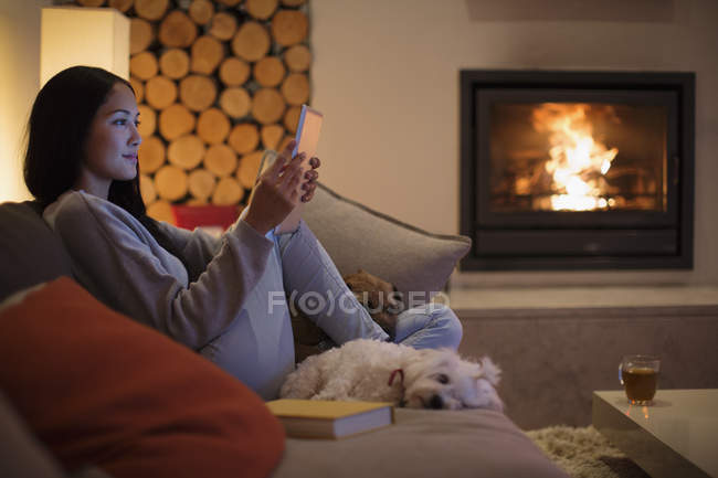 Young woman with dogs using digital tablet on living room sofa — Stock Photo