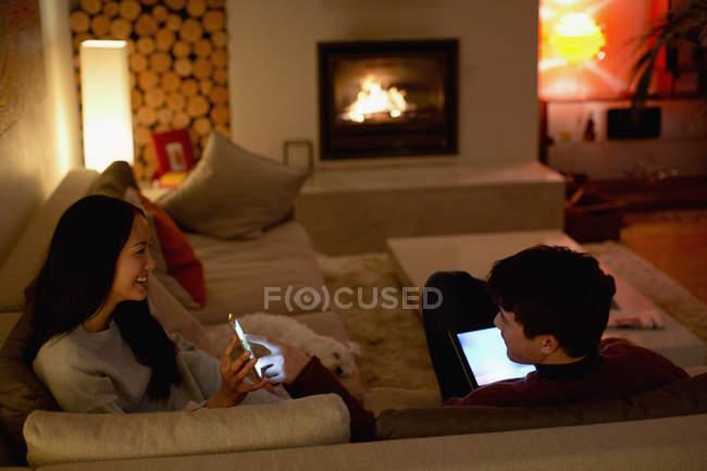 Pares que usam o telefone esperto e a tabuleta digital na sala de visitas escura — Fotografia de Stock