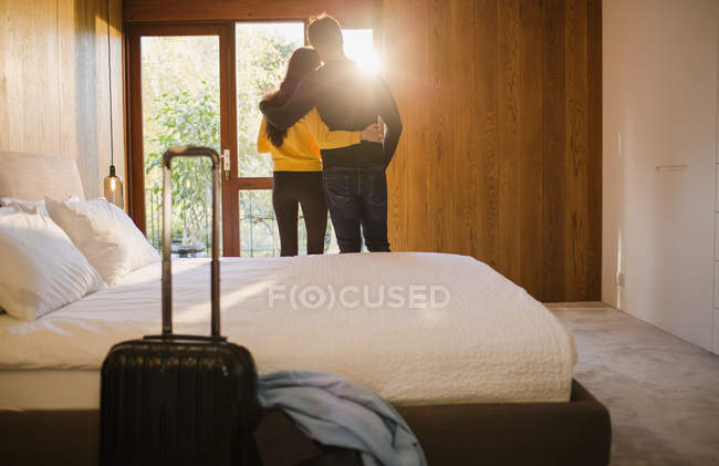 Couple with suitcase hugging in bedroom — Stock Photo