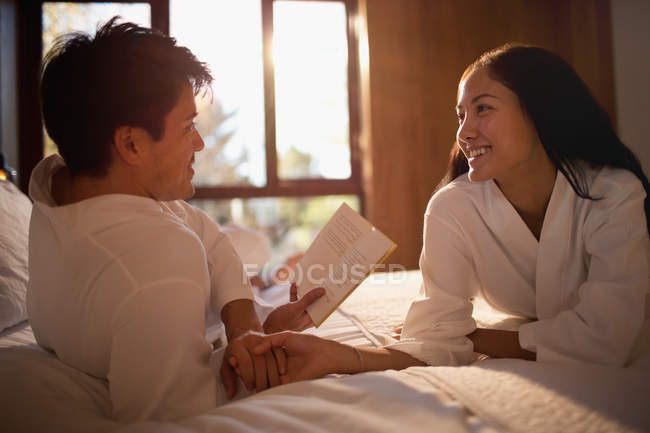 Couple in bathrobes reading book in bed — Stock Photo
