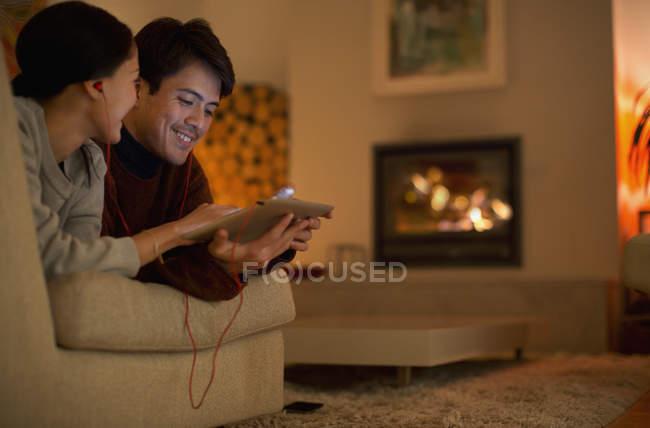 Glückliches Paar mit Kopfhörern teilt digitales Tablet auf Wohnzimmersofa — Stockfoto