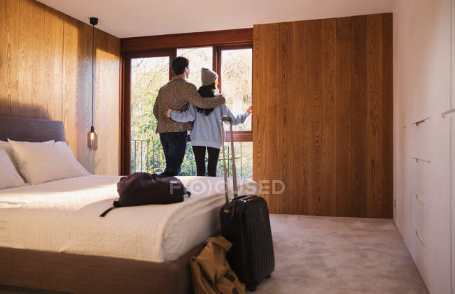 Couple with suitcase looking out bedroom window — стоковое фото