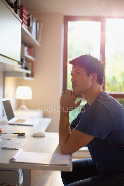 Thoughtful man working at desk in home office — стоковое фото