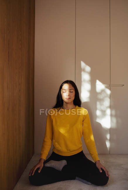 Serene young woman meditating on floor — Stock Photo