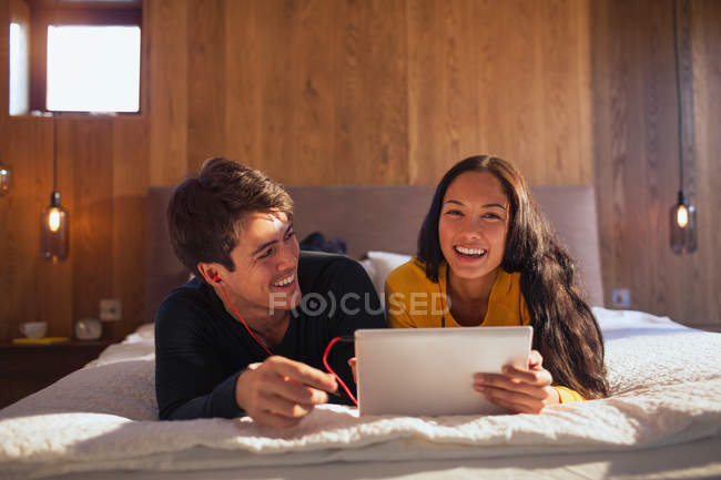 Porträt glückliches Paar mit Kopfhörer teilen Laptop auf dem Bett — Stockfoto
