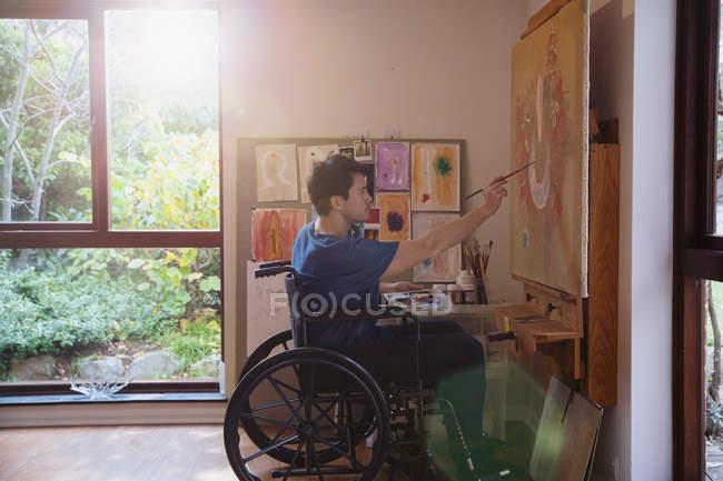 Male artist in wheelchair painting in art studio — Stock Photo