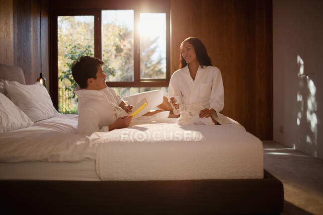Couple in bathrobes relaxing on hotel bed — Stock Photo