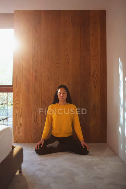 Serene young woman meditating on bedroom floor — Stock Photo