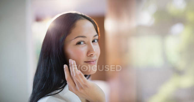 Portrait confident young woman applying moisturizer to face — Stock Photo