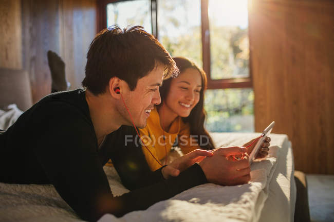 Happy couple with headphones sharing digital tablet on bed — Stock Photo
