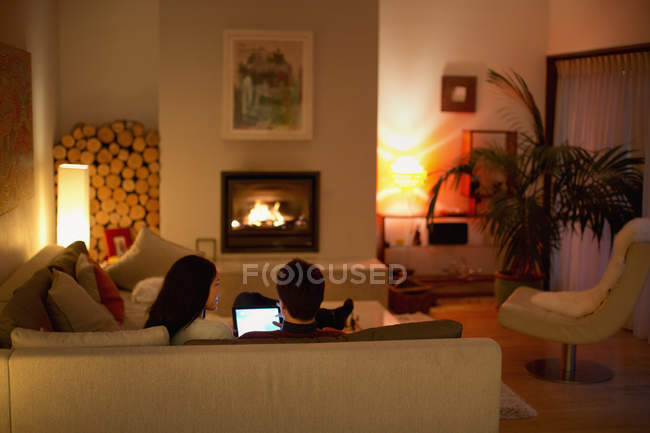 Couple using digital tablet on living room sofa facing fireplace — Stock Photo