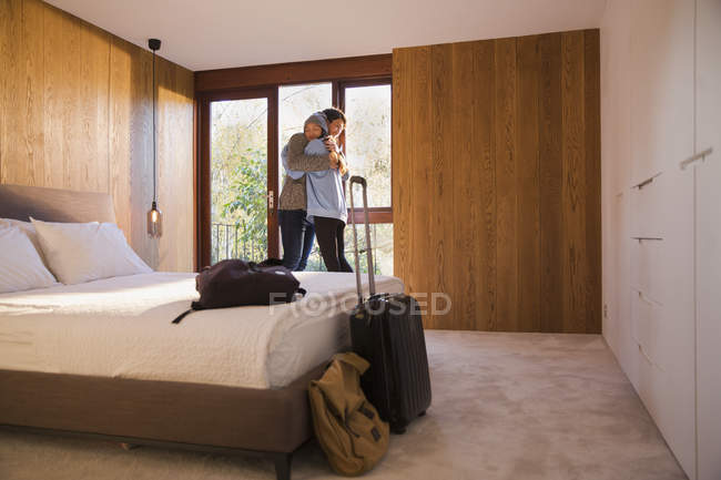 Happy couple with suitcase hugging in bedroom — Stock Photo