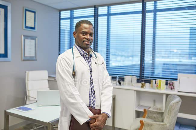 Retrato confiante médico masculino no consultório de médicos de clínica — Fotografia de Stock