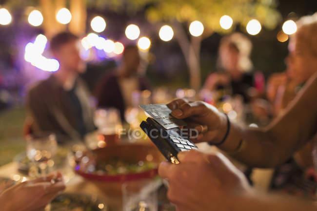 Mujer pagando por la cena con tarjeta inteligente en el patio - foto de stock