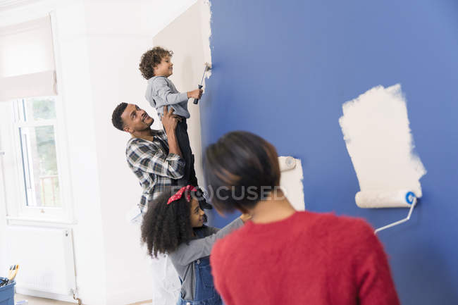 Family painting wall inside new house — Stock Photo