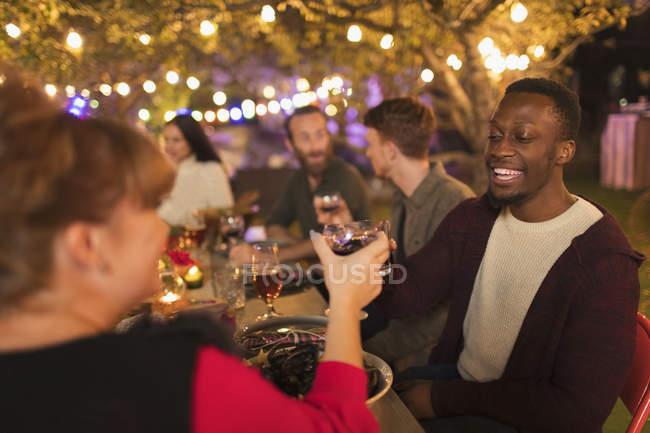 Amigos felizes que brindam vidros de vinho, apreciando o partido do jardim do jantar — Fotografia de Stock