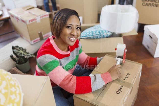 Verticale souriant, femme confiante emballant des boîtes mobiles — Photo de stock