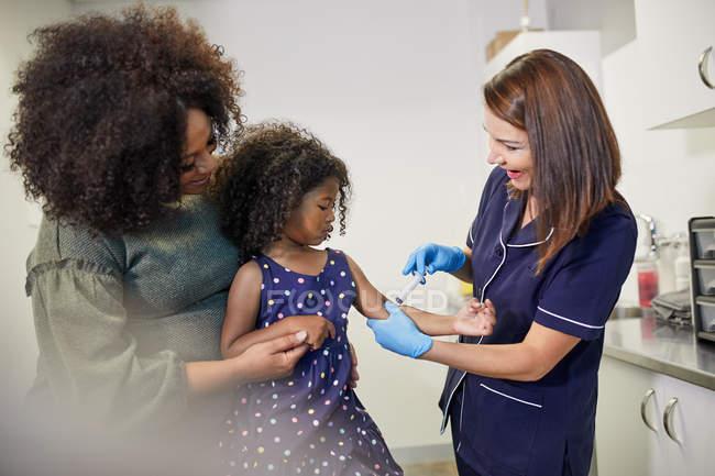 Female pediatrician examining girl in clinic examination room — Stock Photo