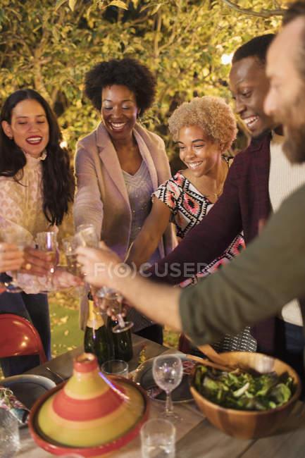 Amigos que comemoram, brindando o champanhe no partido do jardim do jantar — Fotografia de Stock