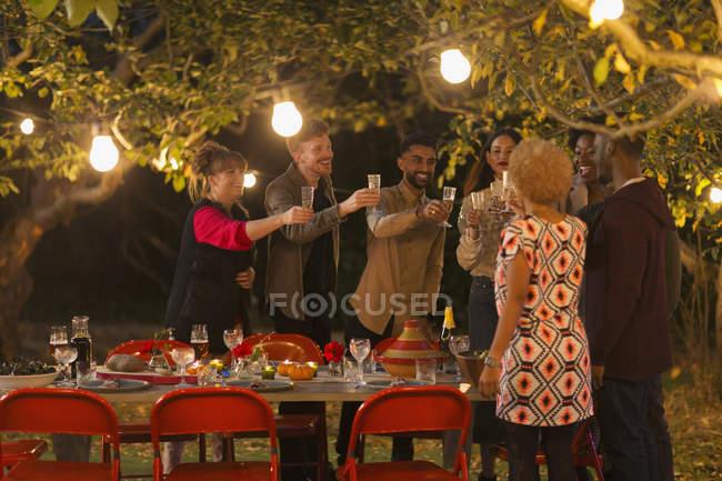 Amigos celebrando, tostando champán en la cena fiesta del jardín - foto de stock