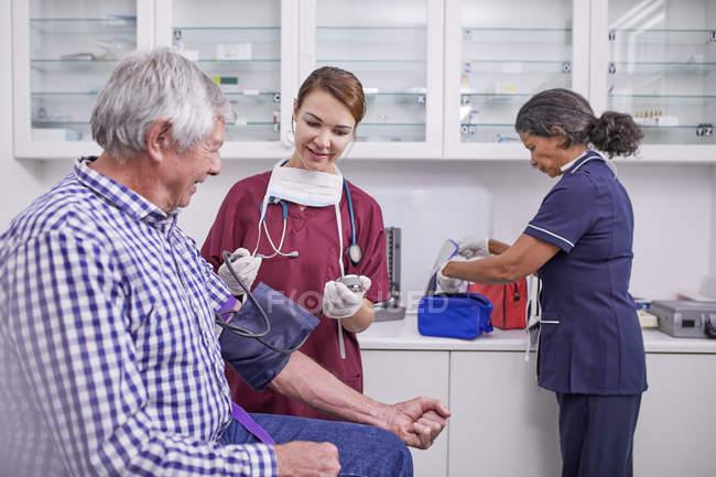 Krankenschwester überprüft Blutdruck eines älteren männlichen Patienten im Untersuchungsraum der Klinik — Stockfoto