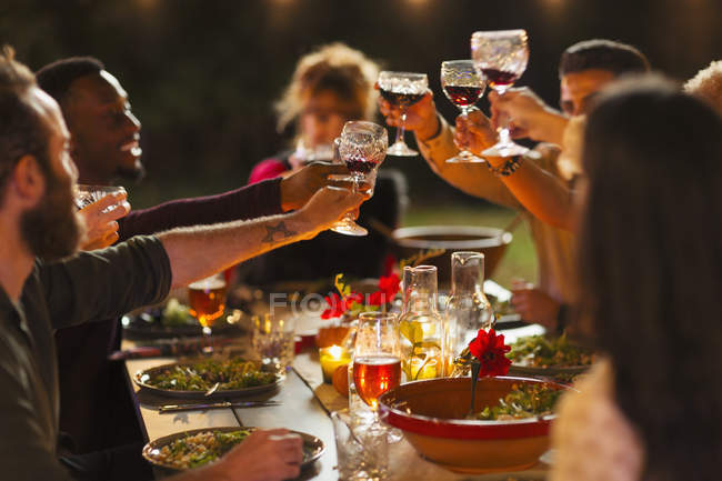 Friends toasting wine glasses at dinner garden party — Stock Photo