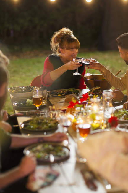 Happy friends toasting wine at dinner garden party — Stock Photo