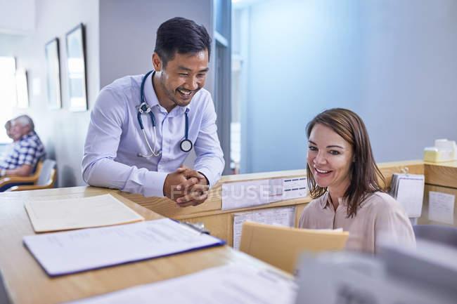 Médecin et réceptionniste souriants discutant du dossier médical à la clinique — Photo de stock
