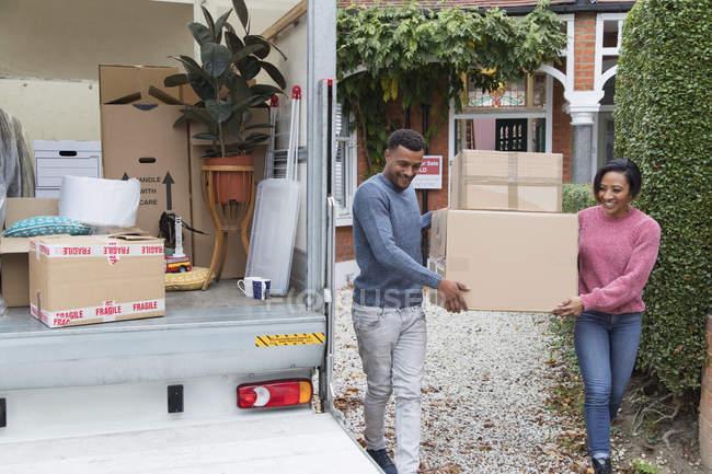 Pareja moviéndose fuera de casa, llevando cajas a furgoneta en movimiento - foto de stock