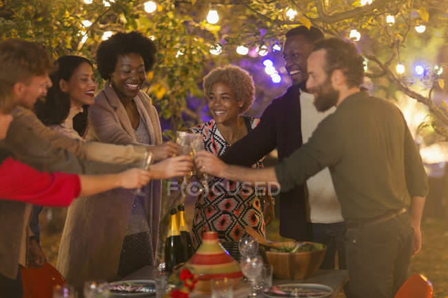 Happy friends toasting wine glasses at dinner garden party — Stock Photo