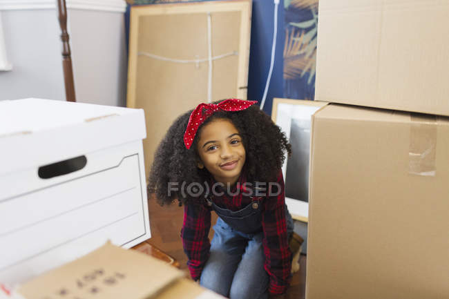 Portrait happy, cute girl among moving boxes — Stock Photo