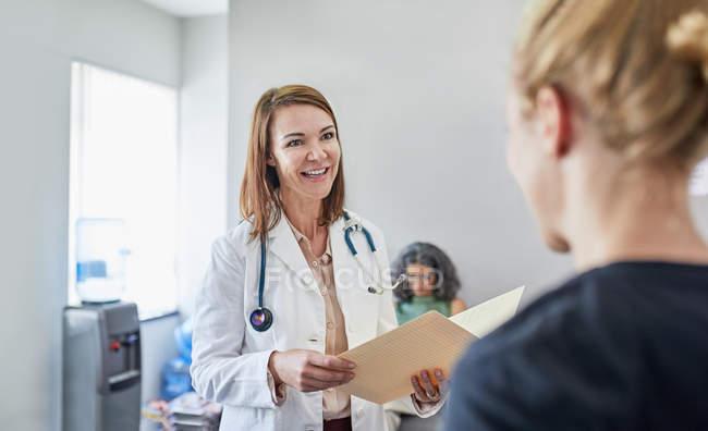 Doutor fêmea e enfermeira que falam na clínica — Fotografia de Stock