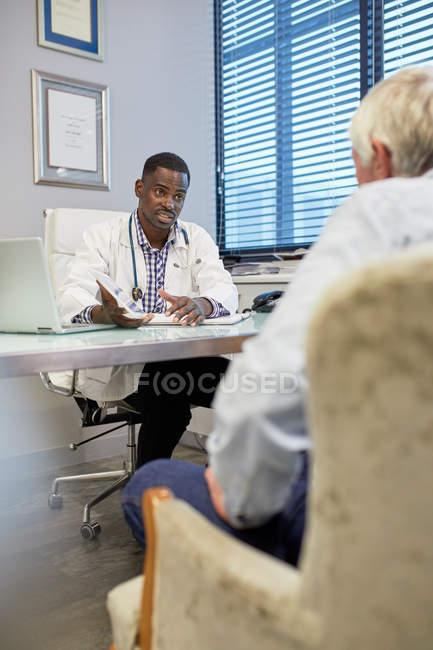 Médecin avec tablette numérique parlant au patient dans le bureau des médecins — Photo de stock