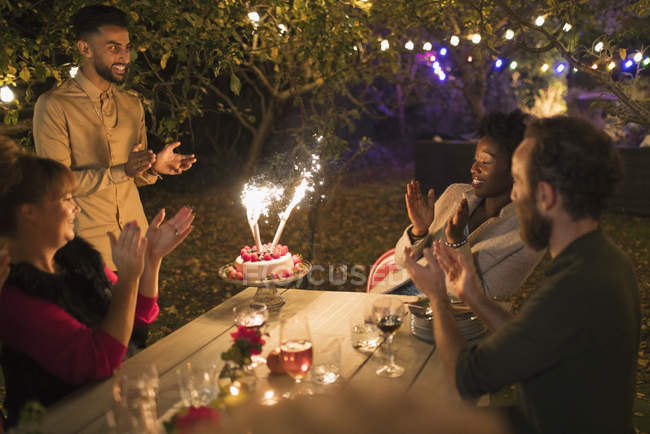 Happy friends celebrating birthday with sparkler cake at garden party table — Stock Photo