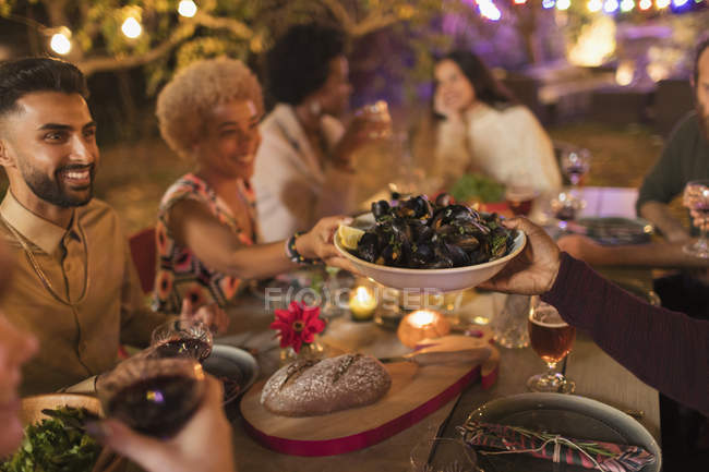Friends passing mussels, enjoying dinner garden party — Stock Photo