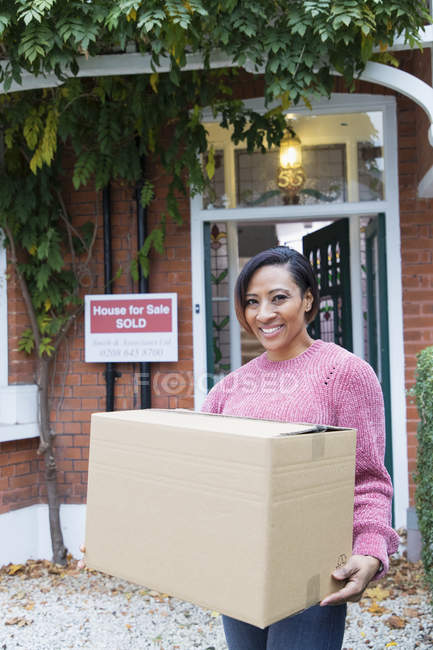 Retrato feliz, mujer segura de sí misma mudanza casa, llevando caja de cartón en la entrada - foto de stock