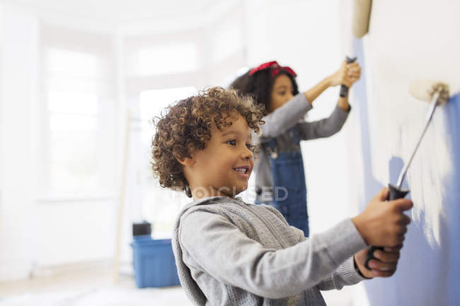 Cute boy painting wall with his sister — Stock Photo
