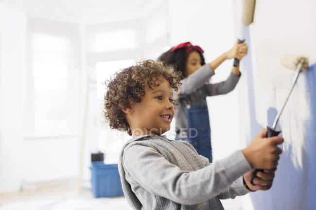 Милый мальчик рисует стену со своей сестрой. — стоковое фото