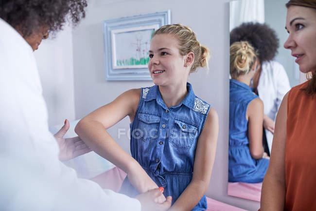 Pédiatre femme examinant le bras de la patiente dans la salle d'examen clinique — Photo de stock