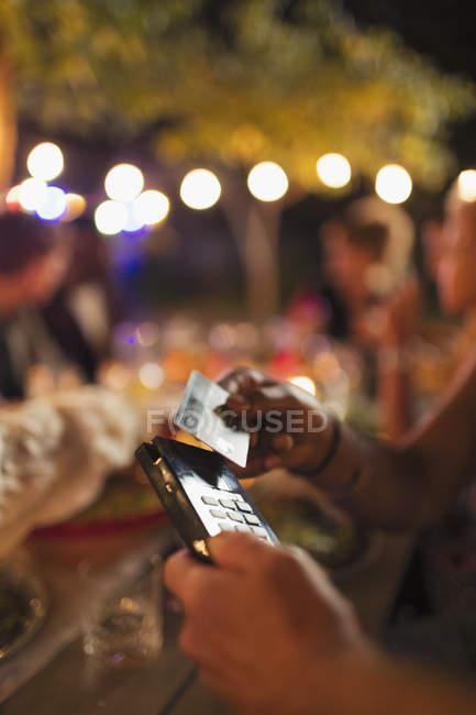 Mujer pagando con tarjeta inteligente en el restaurante patio - foto de stock