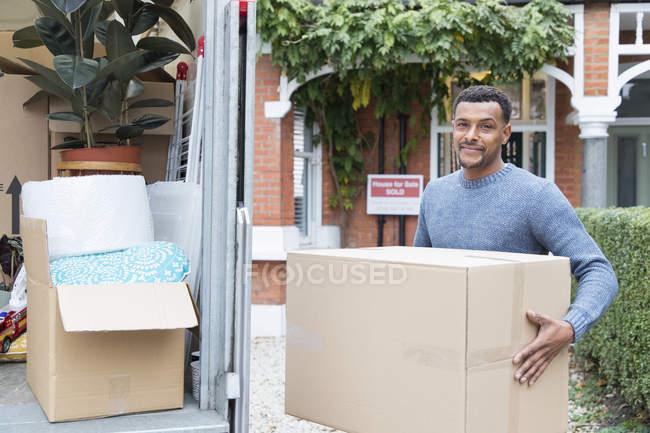 Portrait confident man moving house, unloading moving van — Stock Photo