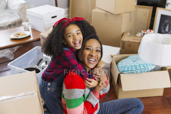 Portrait happy, enthusiastic mother and daughter hugging among boxes, moving house — Stock Photo
