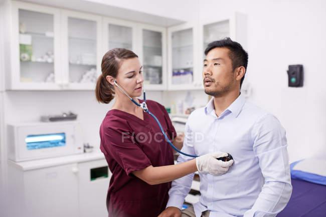 Krankenschwester mit Stethoskop auf männliche Patientin im Untersuchungsraum der Klinik — Stockfoto