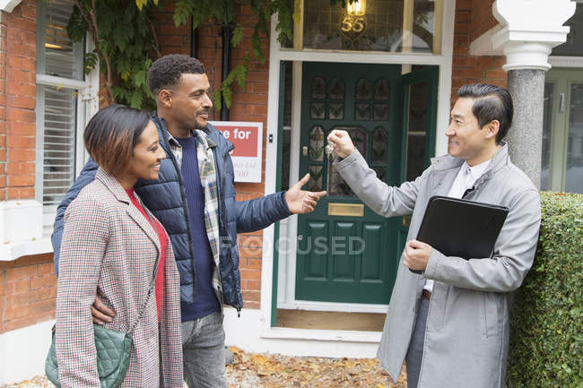 Real estate agent giving house keys to couple outside house for sale — Stock Photo