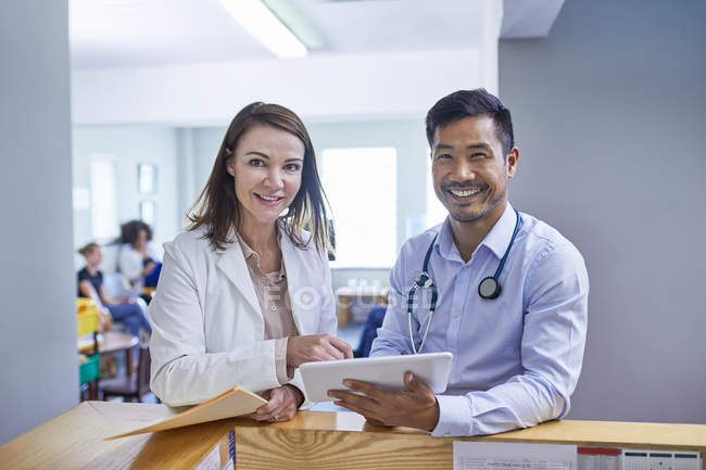 Portrait confident doctors with digital tablet in clinic — Stock Photo