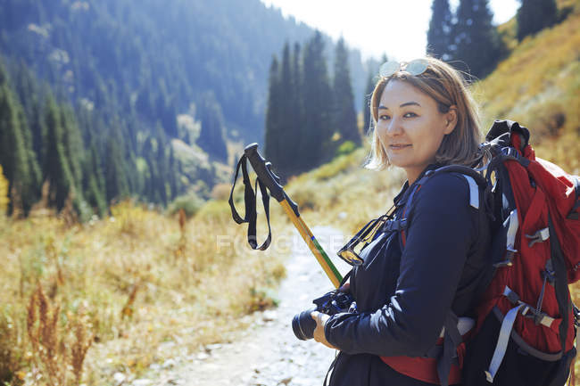Female hiker with backpack and hiking poles travelling in mountain area — Foto stock