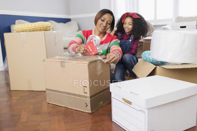 Madre e hija pegando cajas móviles, moviendo la casa - foto de stock