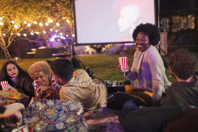Friends eating popcorn, enjoying movie on projection screen in backyard — Stock Photo