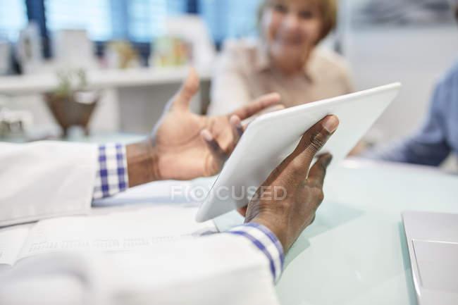 Médecin avec tablette numérique parlant avec le patient dans le bureau des médecins — Photo de stock