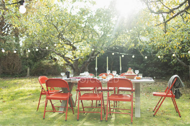 Garden party table and string lights in sunny backyard - foto de stock